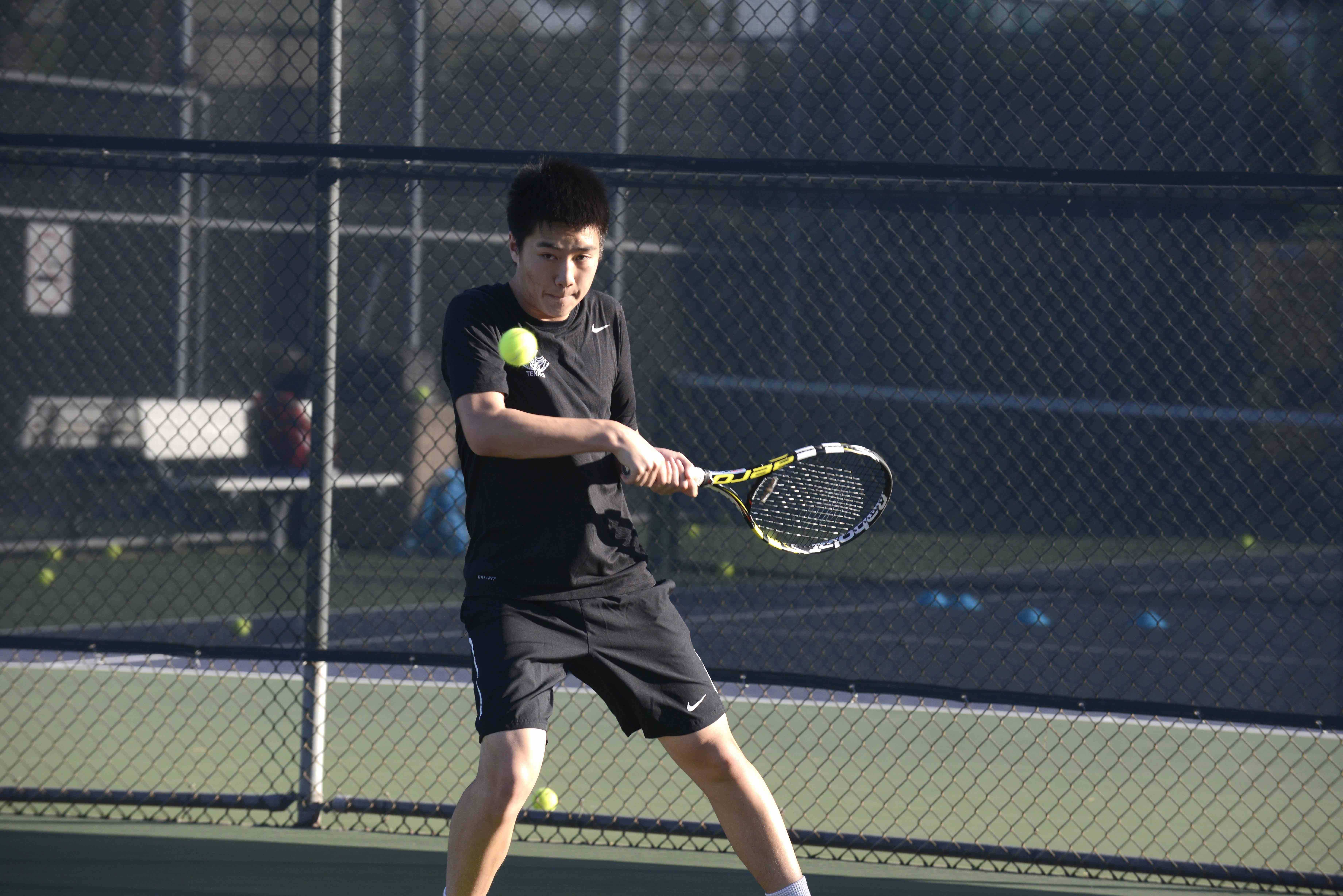 David Wen (11) hits a backhand. He plays number one singles for the Harker varsity boys tennis team.