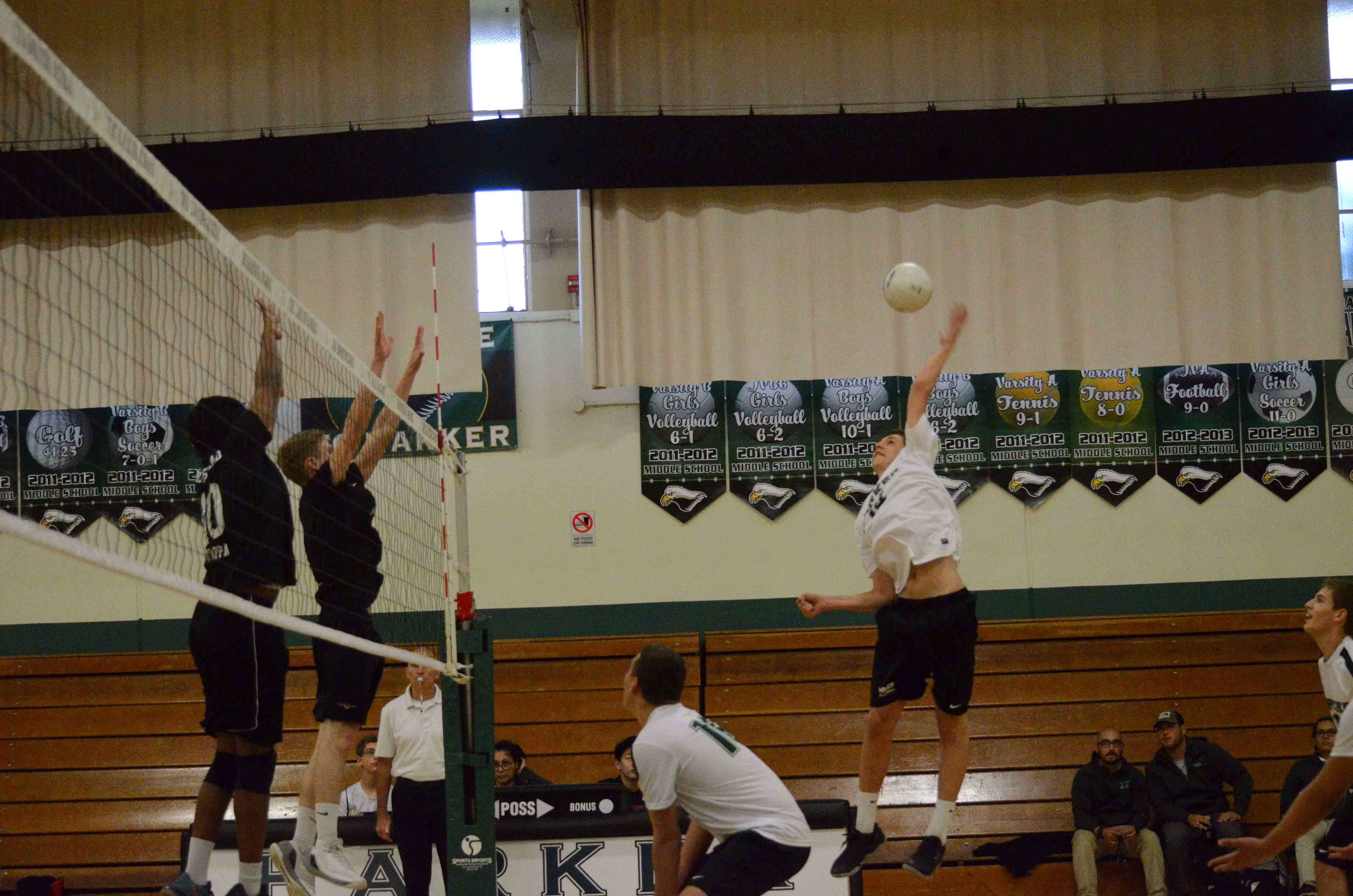 Jarett Anderson (10) prepares to hit the ball against blockers. The boys varsity volleyball team lost to Homestead in five sets.