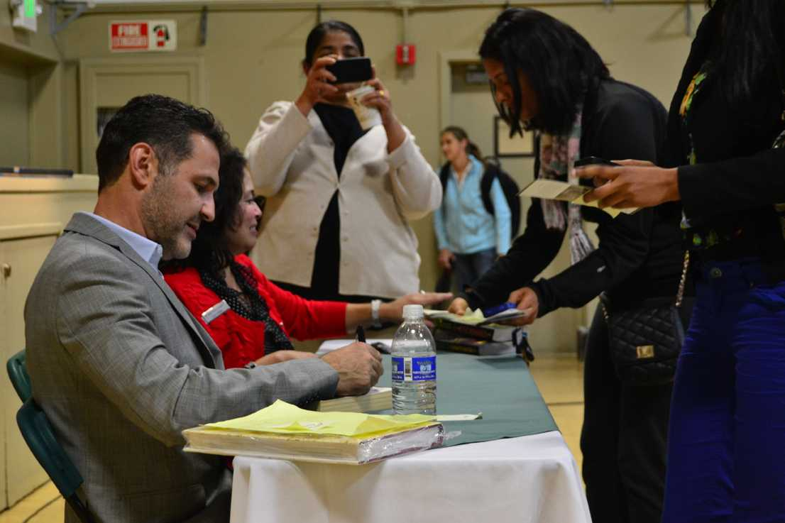 Internationally renowned author and philanthropist Khaled Hosseini signs books after the Speaker Series event. The line of people anxiously awaiting to meet Hosseini spanned the length of the gym.