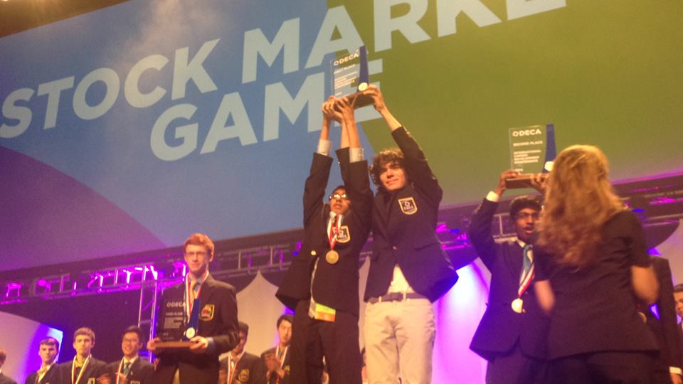 DOWN TO BUSINESS: Nihal Uppugunduri (12) and Alex Tuharsky (11) won first place in the Stock Market Game this year. They accepted their prize recently in Atlanta at DECA's international conference.
