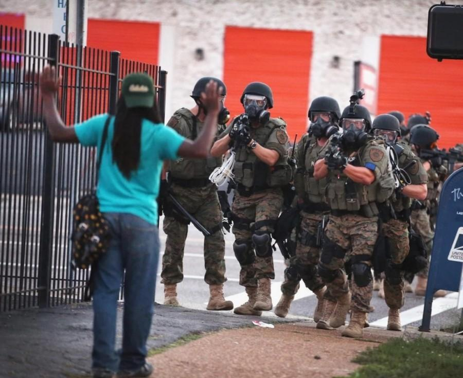 Police in retired Department of Defense (DoD) gear move through the Ferguson business district, forcing protesters to other neighborhoods. The Pentagon's 1033 program, where any state or local law enforcement agency may request DoD equipment, faces intense scrutiny on Capitol Hill this week.