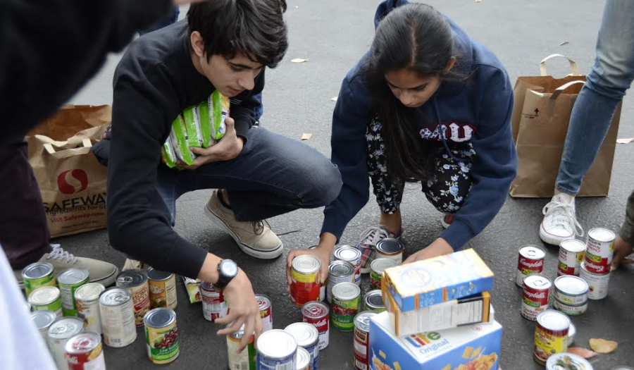 Juniors work with one another to put together the cans their class donated to the food drive.