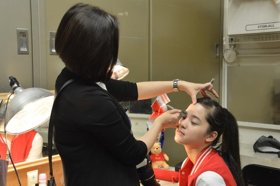 Nana's mother helps her put on makeup before the concert. She performed at a United States International Music Competition Benefit Concert on March 21.