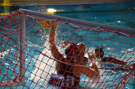 A Harker water polo player blocks the ball from entering the goal.