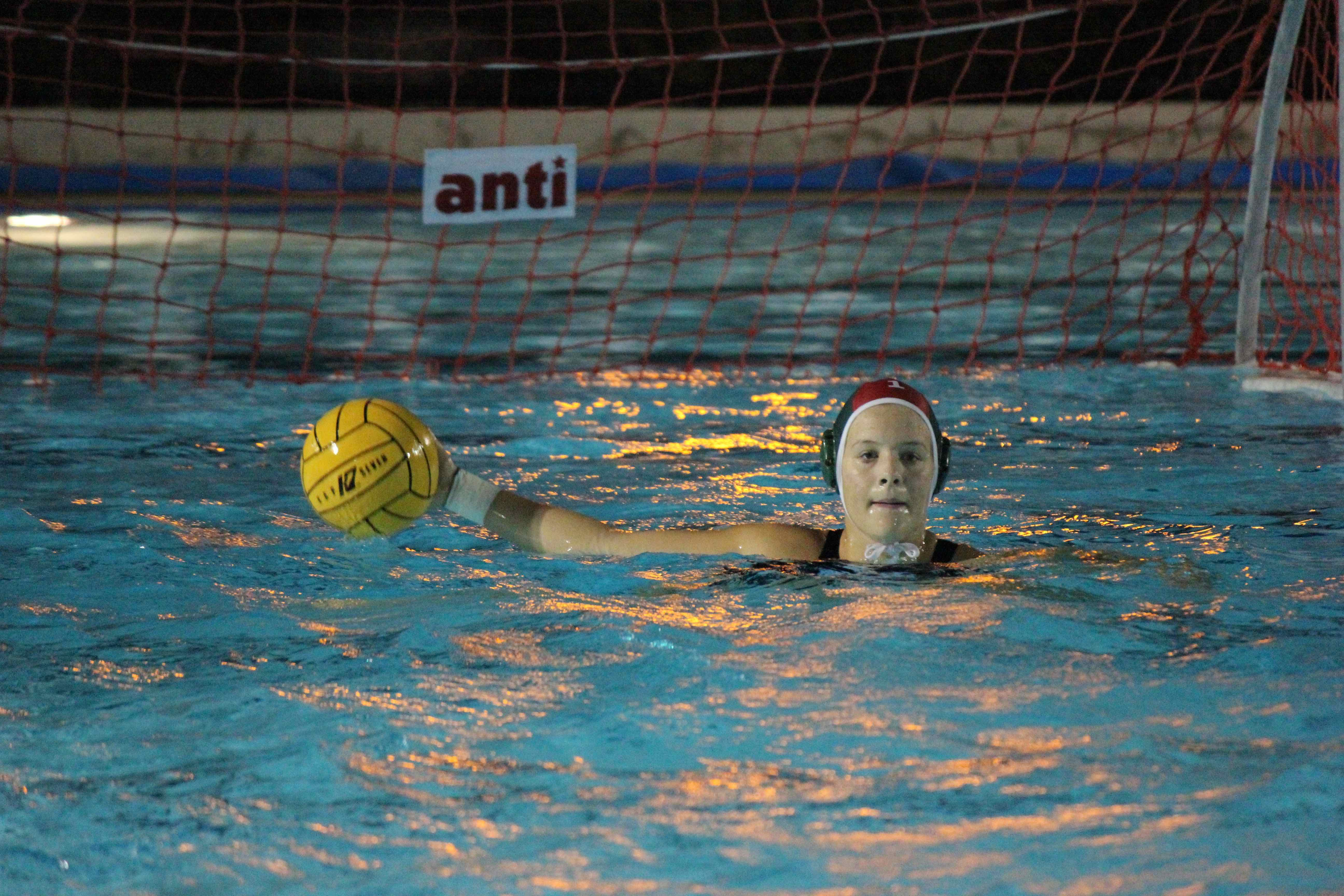 Senior Helena Dworak prepares to throw the ball during the varsity girls water polo game. The Eagles lost the match 1-10.