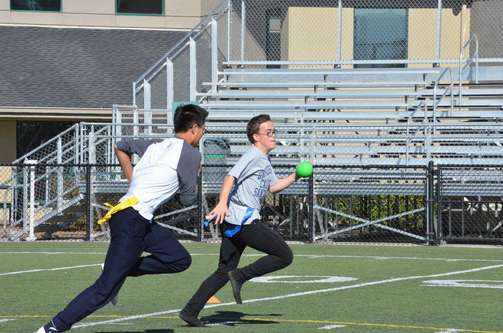 Senior Ryan Fernandez dashes to his side of the field with a ball in his hand while Brandon Mo (10) chases after him to take off one of his flags. Each class competed against each other during long lunch in a game of capture the flag.