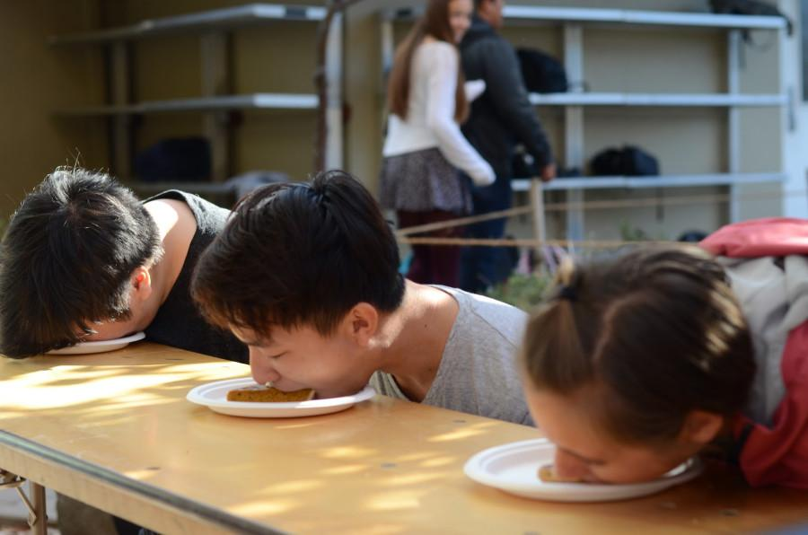 """Arthur Ye (12), Luke Wu (12) and Maile Chung press their faces into the plastic plates. """"When I was eating it I made sure to not look all gross, so when I was sucking it I made sure it didn't get onto outside my lips so I didn't look disgusting,"""" Luke said."""