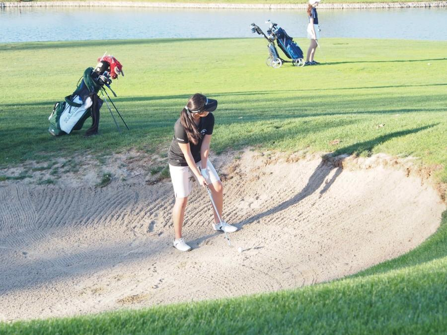 Sophomore Katherine Zhu swings her club in the bunker at the girls' senior night game.