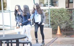 Wearing leggings, Sanjana Marcé (11) walks in the rain along with Trisha Dwivedi (11) and Kshithija Mulam (11). The new dress code was implemented on Nov. 31.