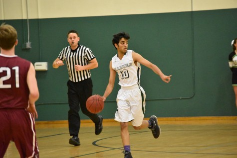 Team co-captain and point guard Rohan Desikan (12) dribbles the ball as he gestures to a teammate. The Eagles' next game is an away league game at Pinewood High School on Friday at 8 p.m.