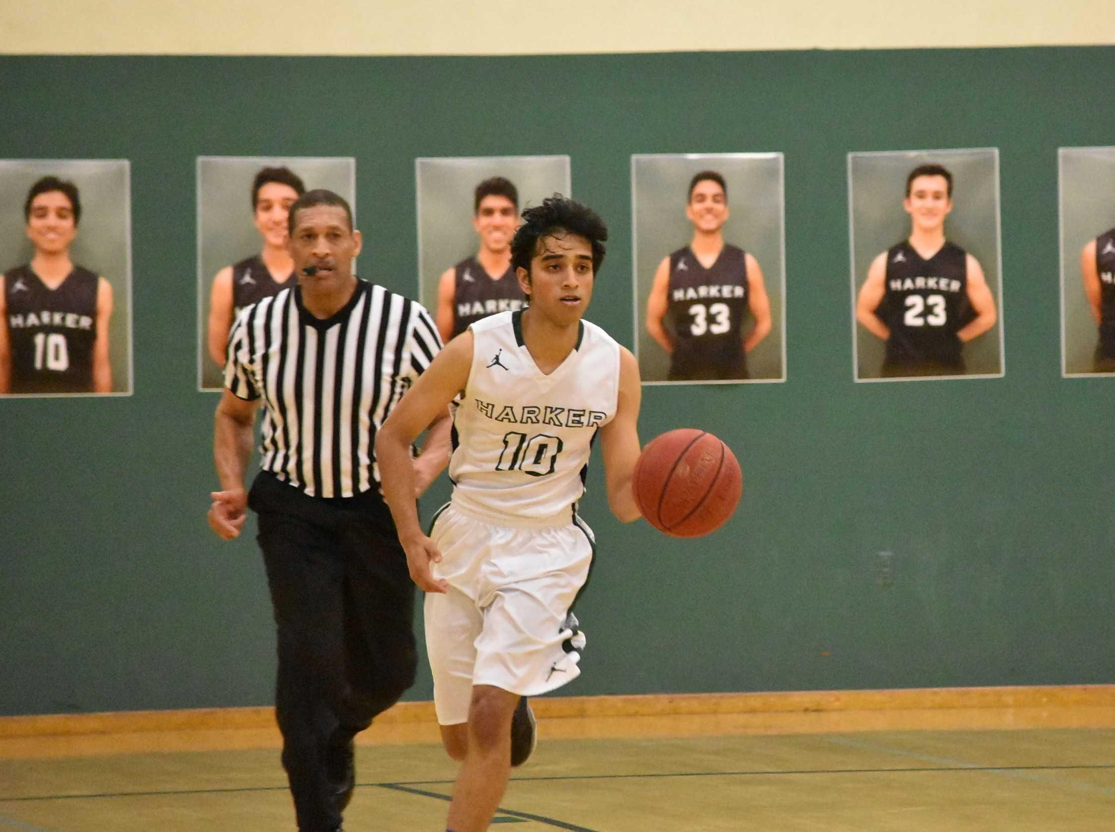 Team co-captain Rohan Desikan (12) runs with the ball. Rohan was one of 14 seniors honored at the joint varsity boys basketball-cheerleading senior night on Feb. 19.