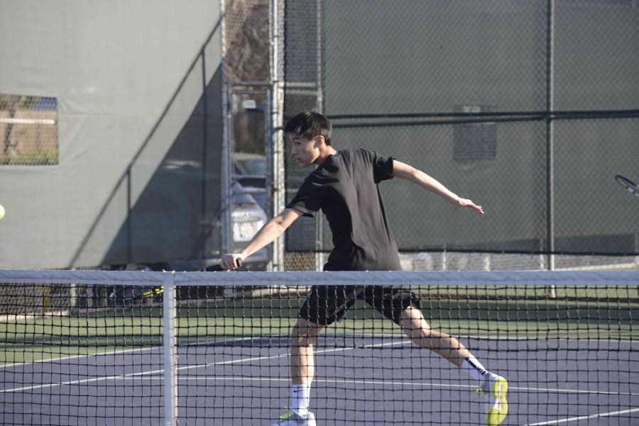 Neil Bai performs a backhand close to the net during his match against King's Academy. The boys won 6-1.