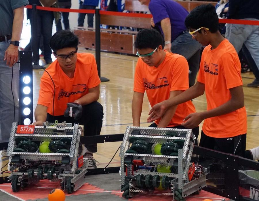 Freshmen Christopher Gong, Andrew Chang and Kaushik Shivakumar consider their robot during a VEX tournament. The team has won multiple awards at both the middle school and high school levels.