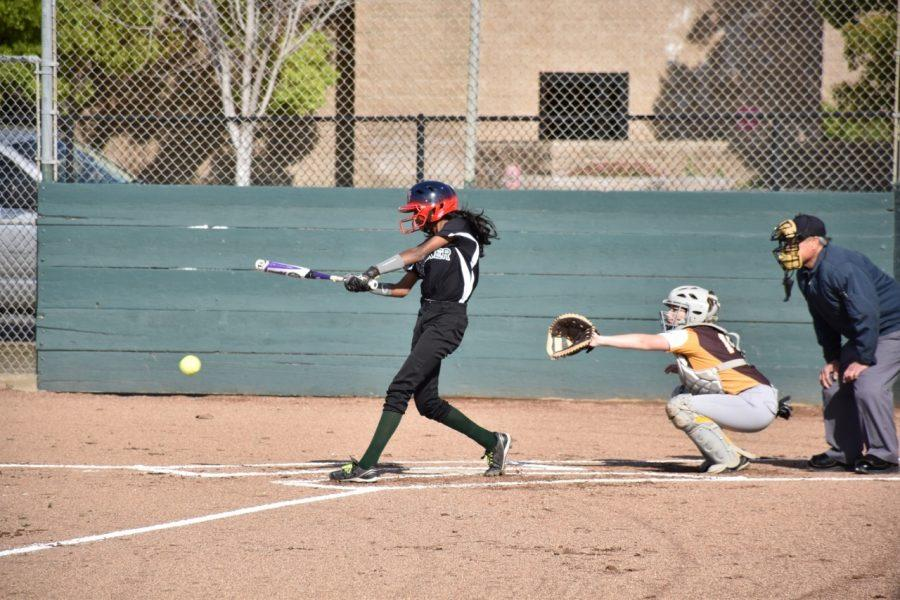 Anika Rajamani (9) hits the softball during a game. The team had a good season, including many blowout wins.