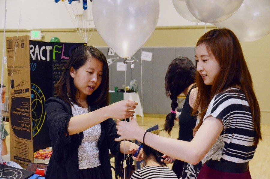 Alice Wu (16) and Kevina Xiao (16) prepare for the 2015 club fair. Both new and returning clubs will be allowed to present at the 2016-2017 club fair.