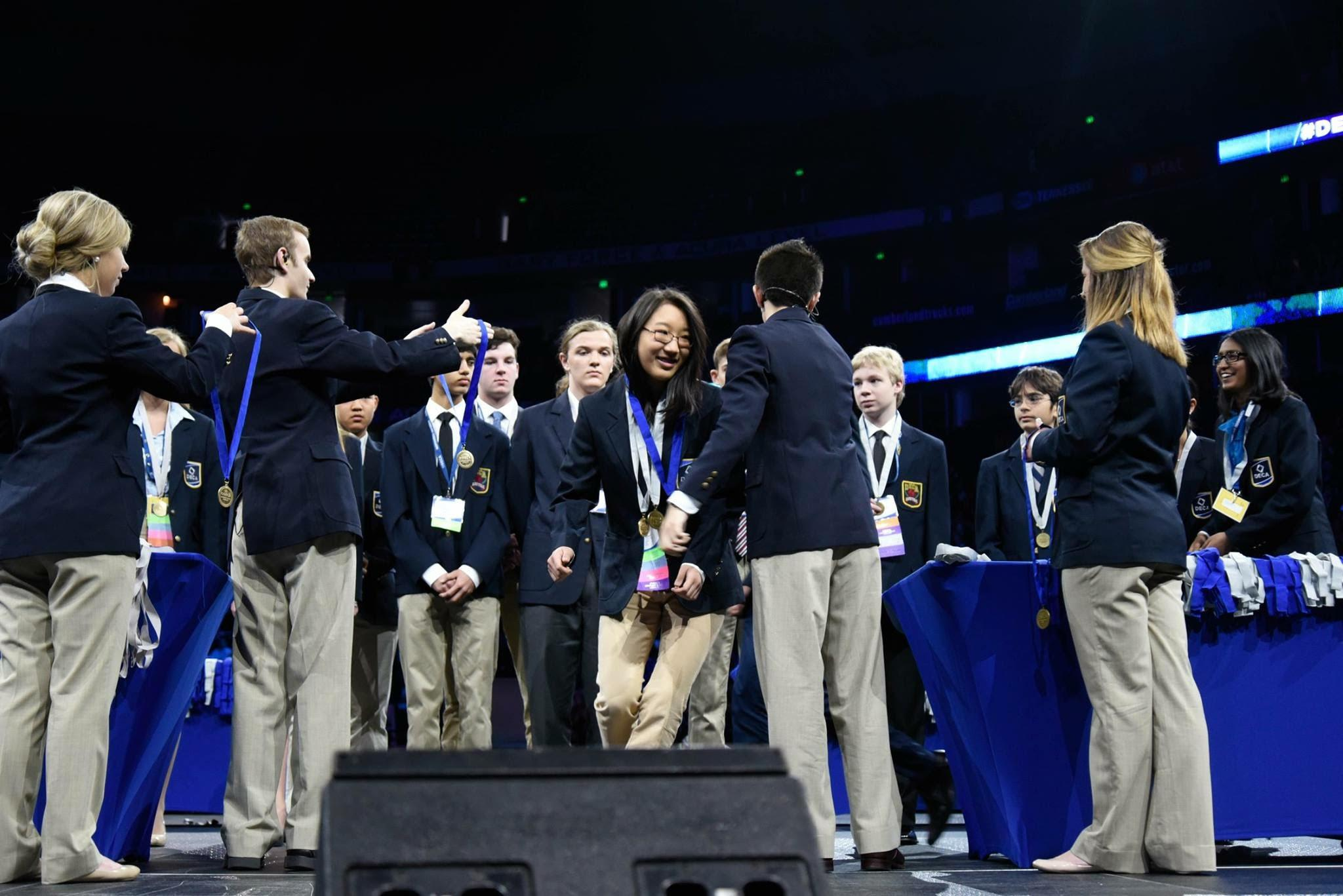 Enya Lu (9) steps forward to receive her medal after being called forward as an overall finalist in Principles of Finance. Later that evening, Enya earned first place, making Harker DECA history.