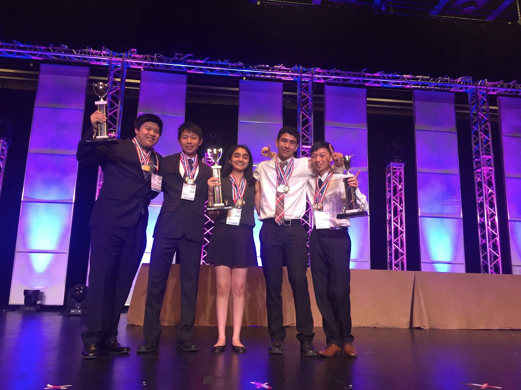 Juniors Michael Kwan, Jerry Chen, Sahana Srinivasan, Shaya Zarkesh and Randy Zhao pose on stage after receiving their first place trophies on June 30. The team placed third in presentation and problem solving and fourth in the essay.