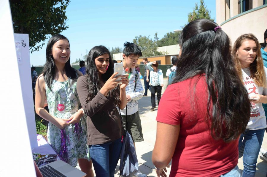 Aliesa Bahri (11) and Millie Lin (11) take a picture of Anusha Kuppahally (10) for FEM Club. The annual Club Fair took place on September 6.