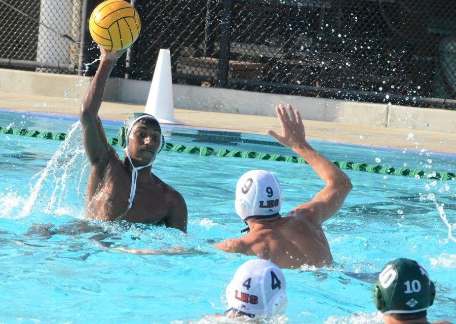 Aadith Srinivasan (11) throws the water polo ball. The varsity water polo team is currently 11-2 in league and 15-5 overall.