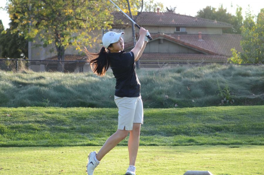 Katherine Zhu (11) hits the golf ball. The girls golf team is currently 8-2 in league and 9-3 overall.
