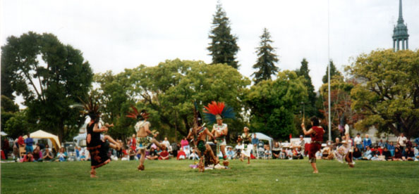 Tribal members deliver one of the dances of the ceremony at the first Indigenous Peoples Day celebration and pow-wow in Berkeley in 1993. The dances performed included the men's Fancy Dance, consisting of intricate footwork, and the Jingle Dance, a healing dance in which dancers perform dressed in row upon row of chiming cones. ​