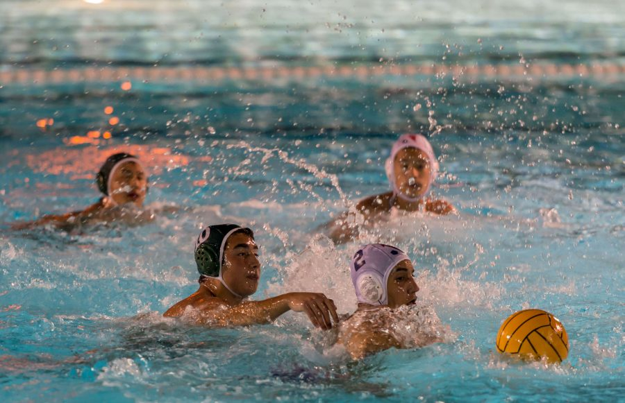 Matthew Hajjar (10) reaches for the ball during the varsity boys water polo game. The team worked hard in order to achieve its win.