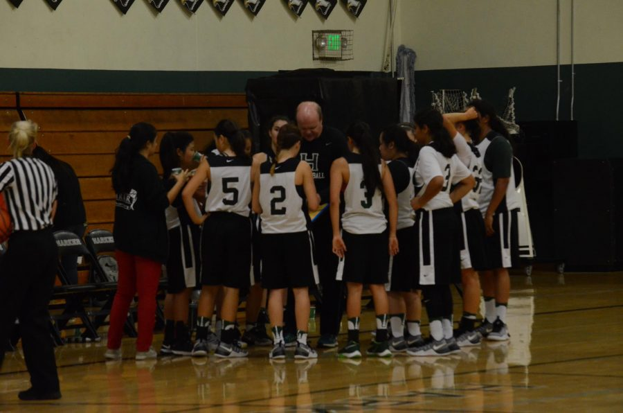 The girls basketball team huddles during a time-out. The team played its first game today in a scrimmage against Aptos High School today.