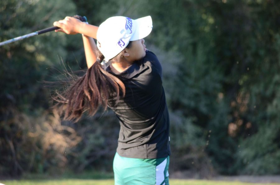 Senior Vienna Wang follows through after hitting the golf ball. The girls golf team ended its season with a ninth place finish at the CCS championships in Carmel.