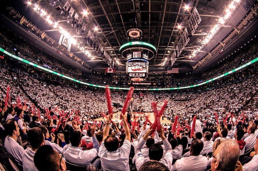 Toronto Raptors fans cheer on their team during the NBA playoffs by waving stick-shaped balloons in their team colors. Basketball teams can generate huge amounts of value for local businesses and communities.