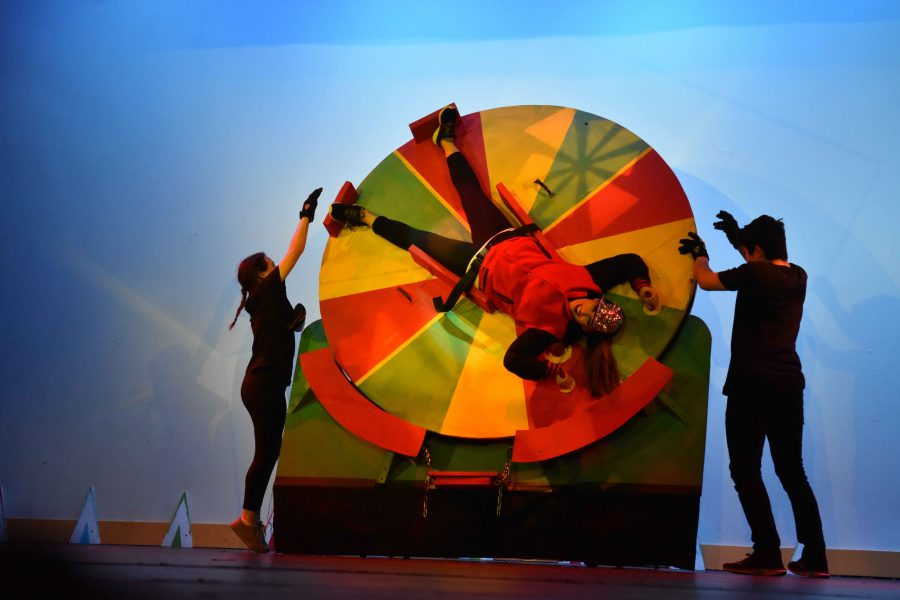 Stage crew members Tamar Sasson (10) and Logan Frank (10) spin cheerleading coach Jill Bettencourt on a wheel at the beginning of the teachers' dance