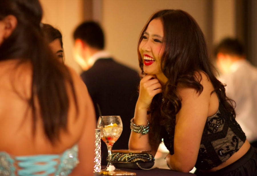 Liana Wang (11) smiles as she talks to other students at prom. Other than participating in the prom activities, students interacted and mingled with friends.