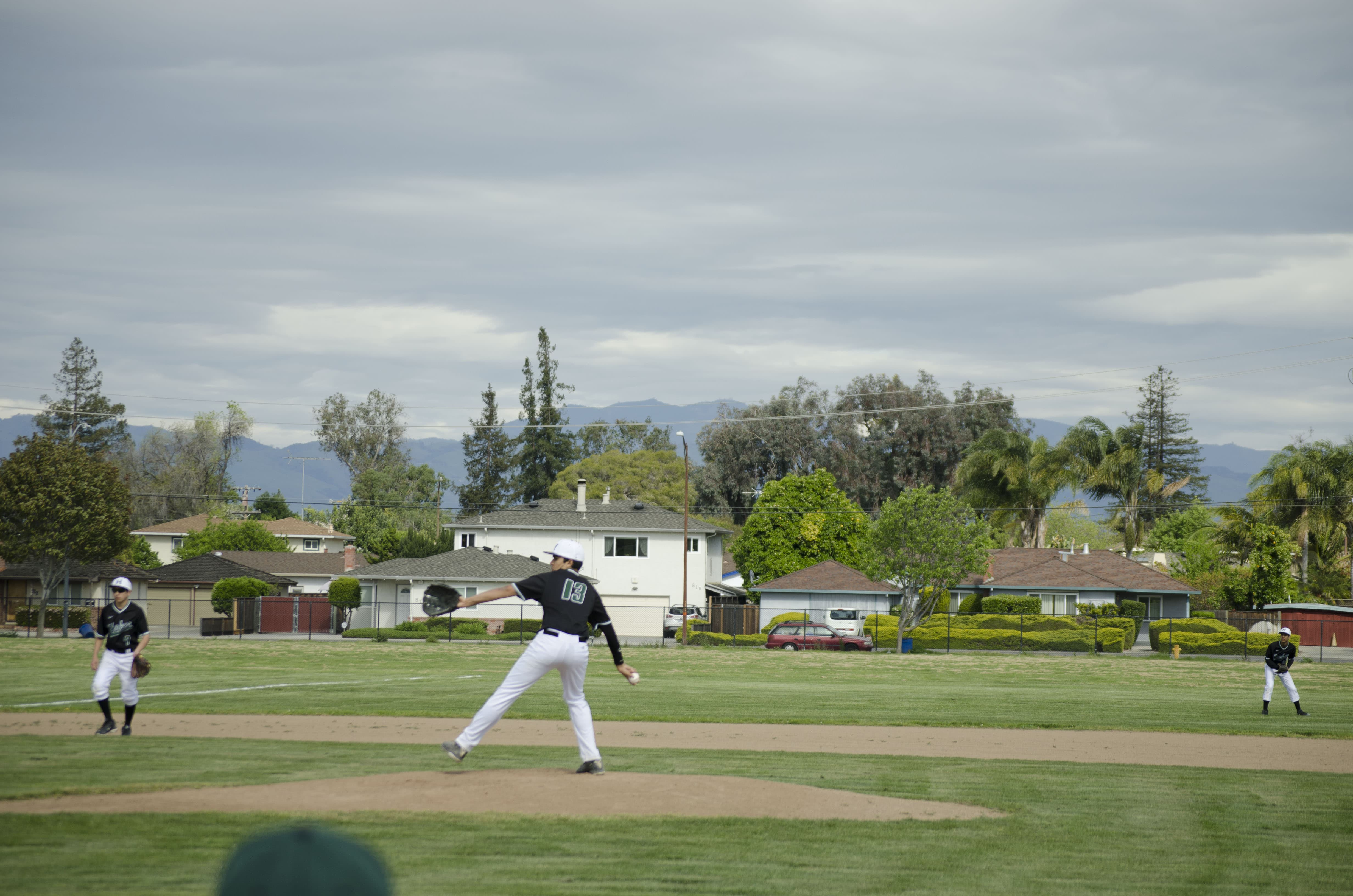 Pitcher Varun Haltore (12) prepares to throw a pitch. Varsity boys baseball lost 0-4 against Mills High School
