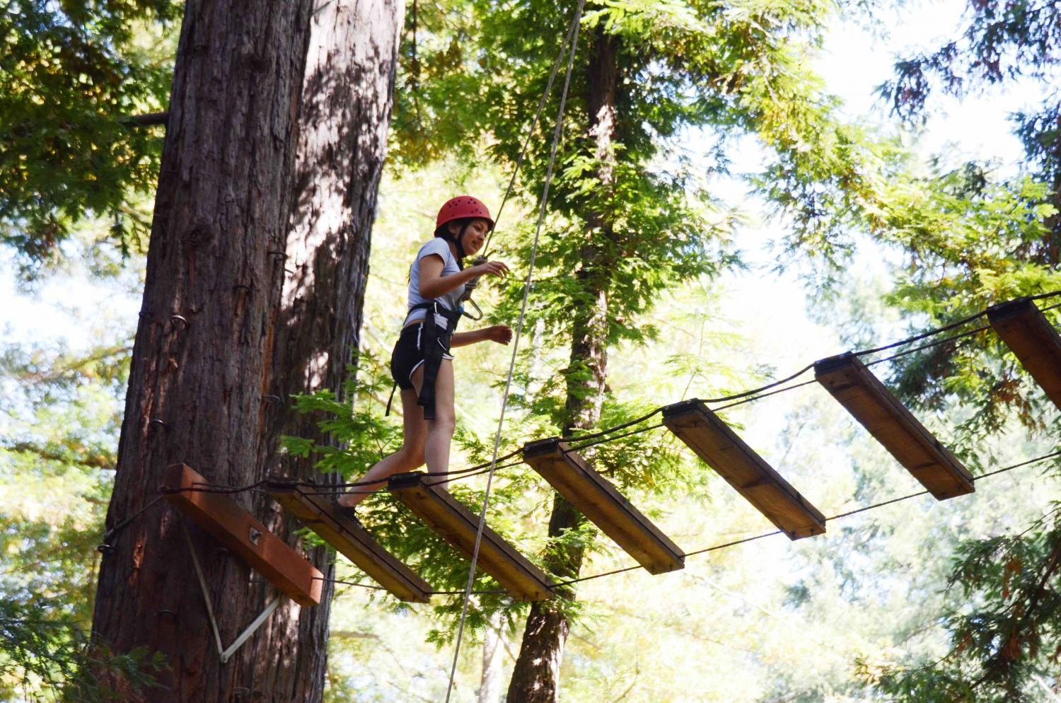 Reiya Das (10) crosses the Incomplete Bridge, a series of wooden planks strapped between two trees. This was one of many rope courses offered throughout the day.