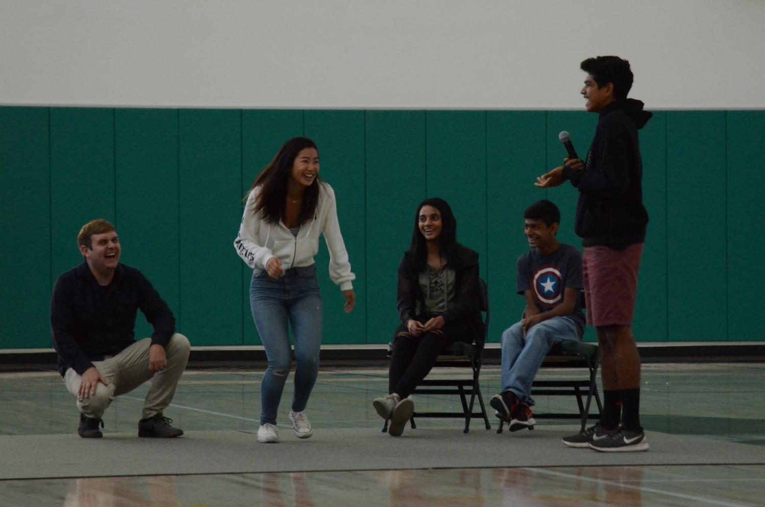 Director of Upper School Clubs Eric Kallbrier and charades team Meena Gudapati (12) and Akshay Manglik (9) laugh as Elizabeth Yang (11) attempts to act something out for teammate Mihir Sharma (10). Elizabeth and Mihir won the charades game.