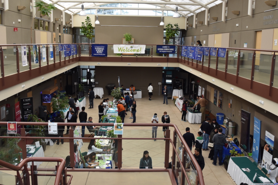 Students and faculty visit booths at last years Research Symposium in Nichols Atrium. Similarly to this event, the Artificial Intelligence Club plans host a series of workshops and lectures about biology, math, computer science and a variety of other topics.