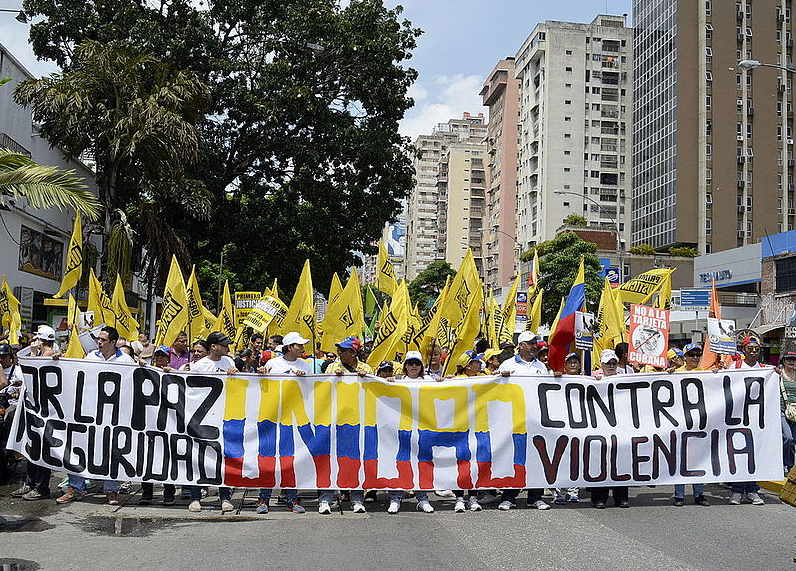 Protesters at an October 2014 demonstration in Venezuela carry yellow flags and a sign. Plummeting oil prices caused Venezuela's economy to crash, resulting in high inflation, a lack of basic necessities and an increased crime rate.