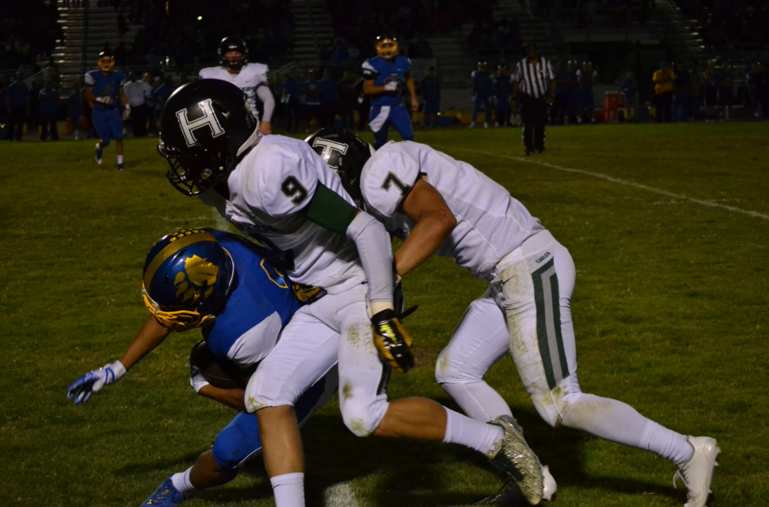 Anthony Contreras (12) and Jared Anderson (11) tackle a Santa Clara player running the ball. Both Anthony and Jared scored touchdowns during the first half of the game.