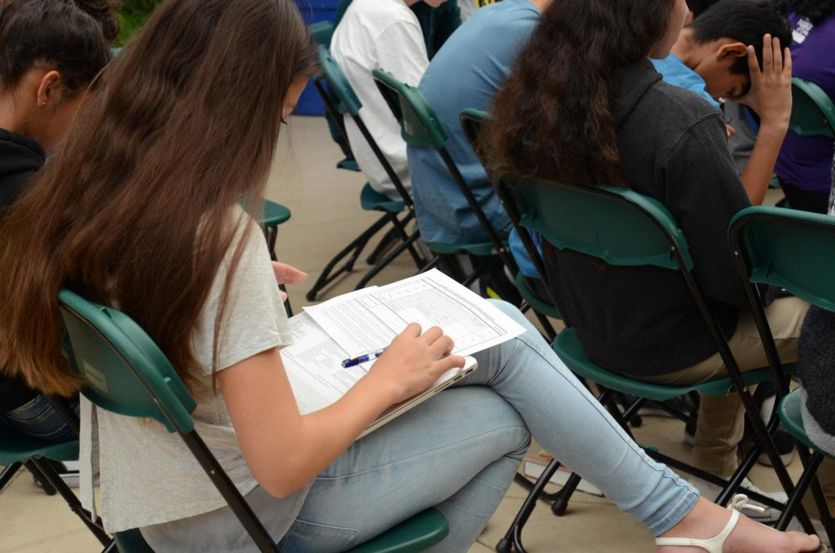"Zoe Kister (9) completes her paper course plan near the end of the LIFE assembly. ""Mr. Barth particularly does a good job of saying that it's possible to do too much. If you take all the classes, you miss the important part of having a creative educational life,"
