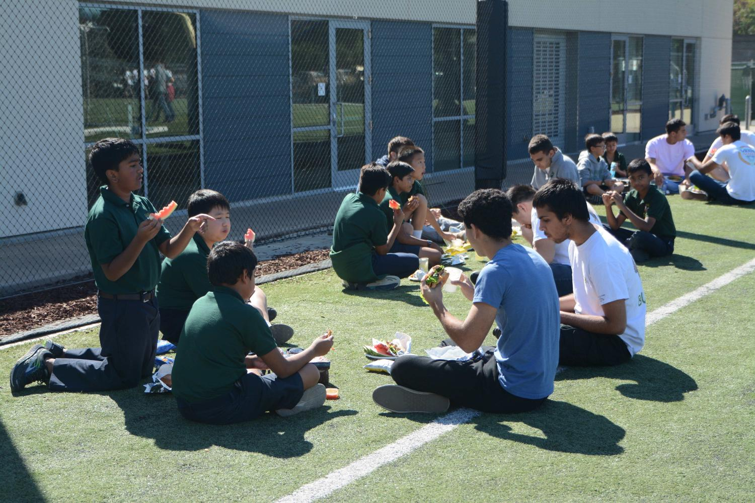 Seniors and their Eagle Buddies enjoy lunch on Davis Field. Students were allowed to eat on the turf and on the bleachers facing Shah.