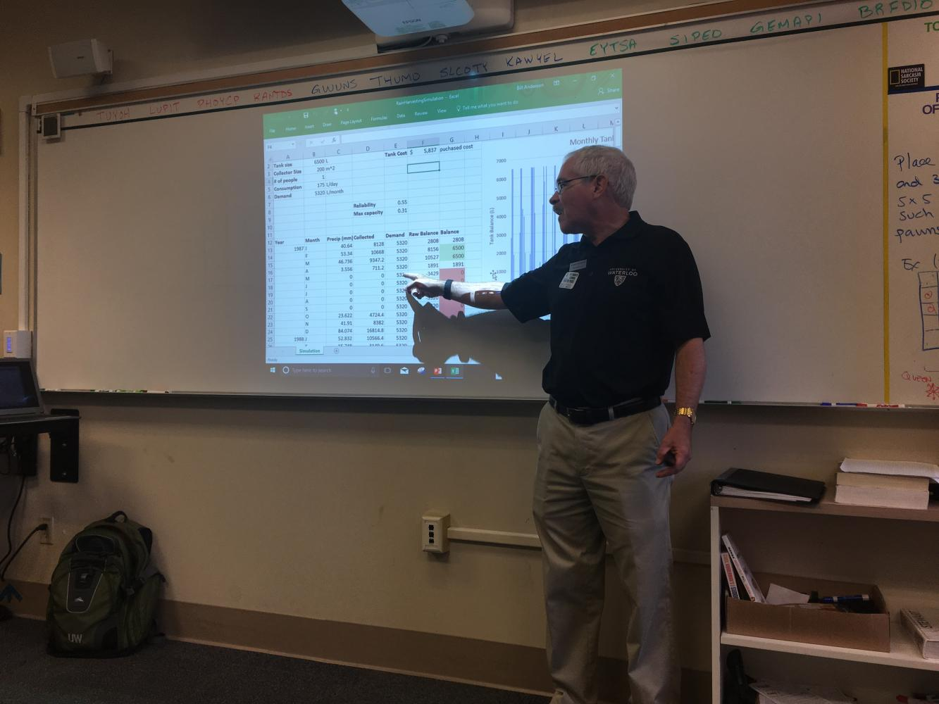 Professor Bill Anderson points to a spreadsheet during his presentation. Anderson discussed engineering and design for two fifth-period math classes.