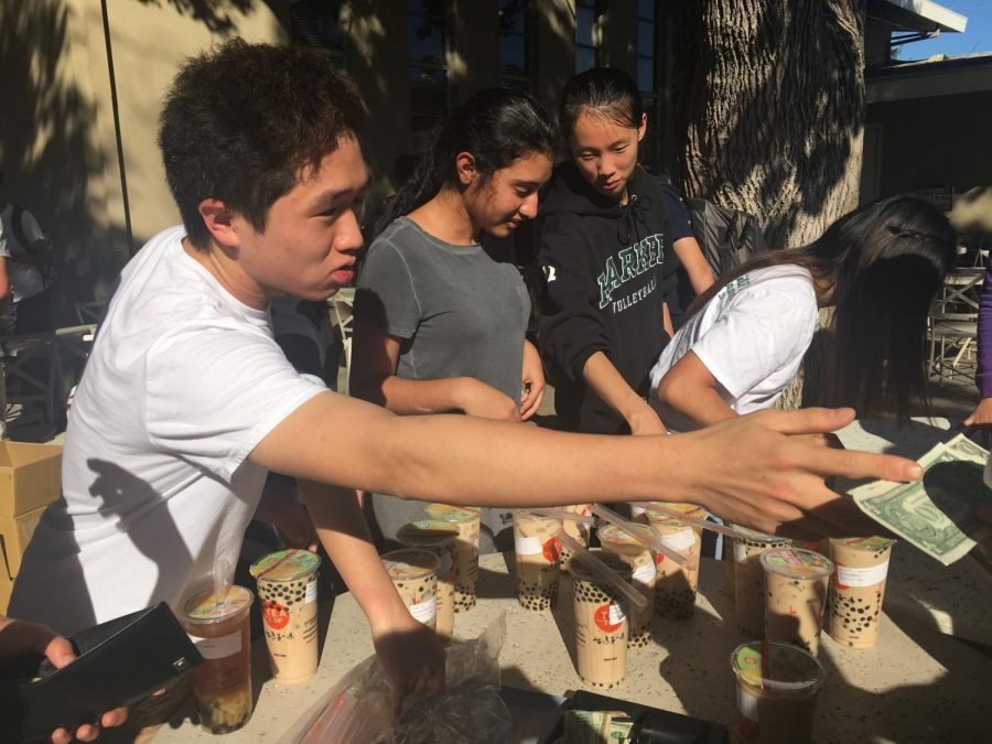 Tri-M co-president Jeffrey Yang (10) takes money from a student buying boba at the clubs fundraiser outside Manzanita after school on Tuesday. Tri-M sold pearl milk tea from Tea Top on Tuesday and Thursday.
