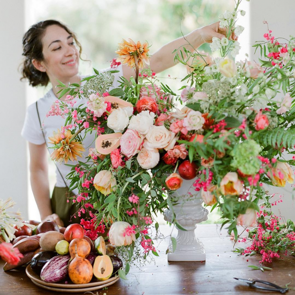Kiana Underwood arranges a summer floral piece with pink, beige, orange, green, and red accents. She grew up surrounded by flowers, including the garden of her grandfather.
