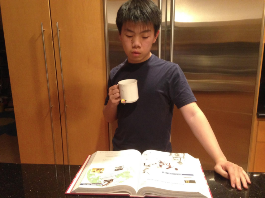 Markus Wong (12) reviews his biology textbook in preparation for the 2017 spring final exam while drinking earl grey tea. Markus drinks tea to obtain a caffeine boost to stay awake when he studies late at night.