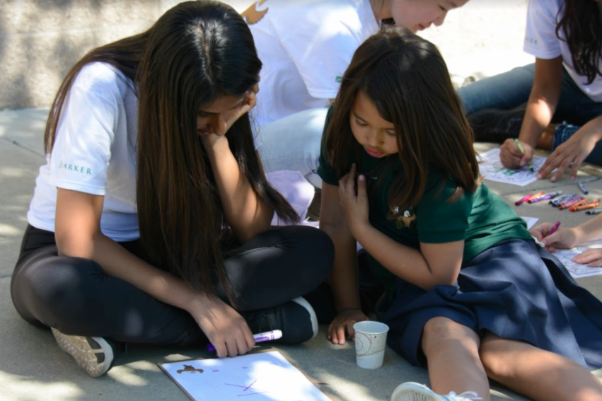 Zara Vakath (10) and her Eagle Buddy draw with markers. The Eagle Buddies program is run by upper school math teacher Jane Keller.