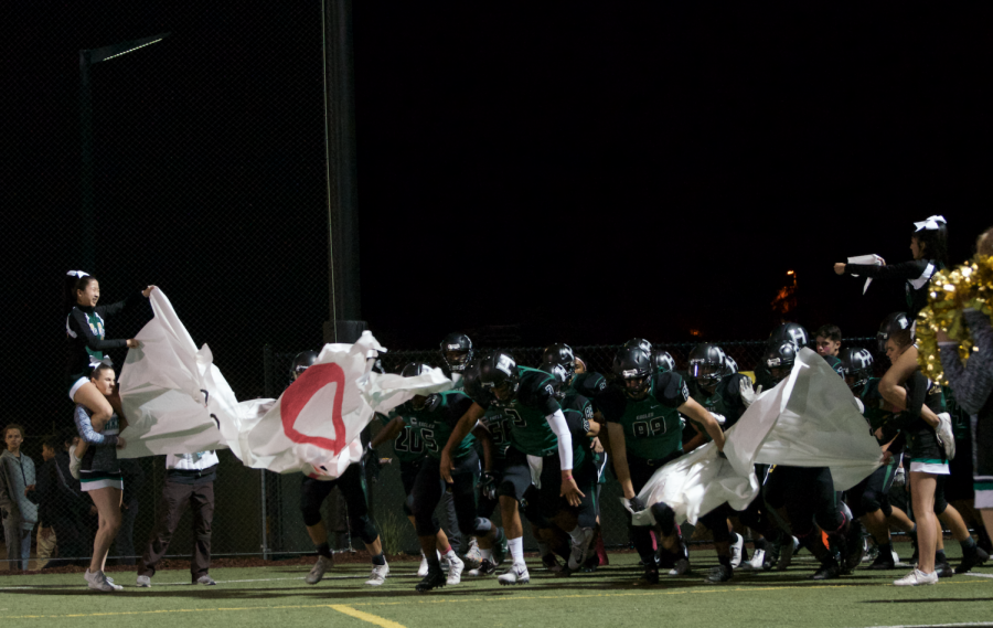 The+varsity+football+team+breaks+through+the+poster+after+halftime.+The+team+is+still+undefeated+after+their+win+against+Lindhurst.