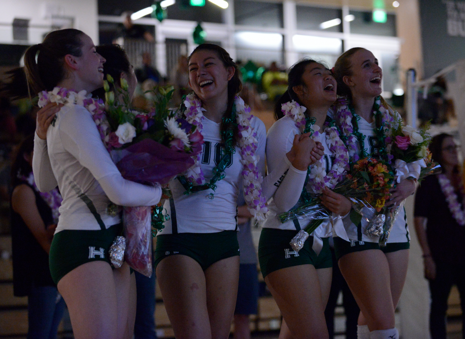 Seniors Lauren Napier, Melissa Kwan, Megan Cardosi, Tiffany Shou and Isabella Spradlin laugh while watching a video honoring their achievements. All five seniors have played volleyball all four years of high school.
