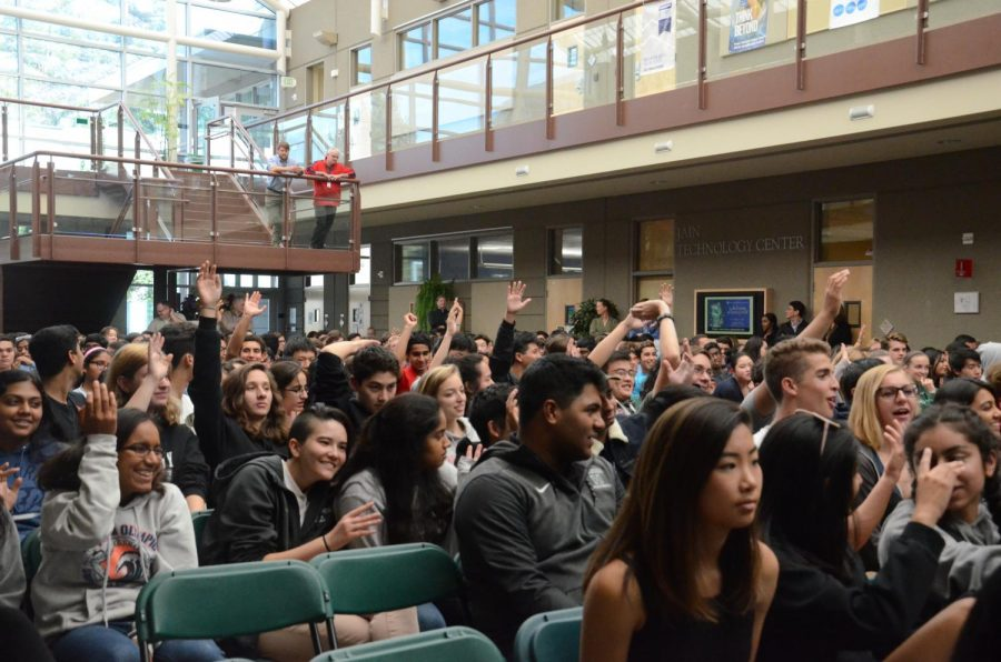 Members of the senior and junior classes raise their hands in the air in response to one of Johnston's questions about community expectations. Johnston also led the students and their attending advisors in a snapping game and asked them to raise their hands in the air and snap if they were familiar with the terms gender, gender roles, gender stereotypes, gender expression, gender identity, gender non-conforming and a variety of others she projected one by one on the screen behind her.