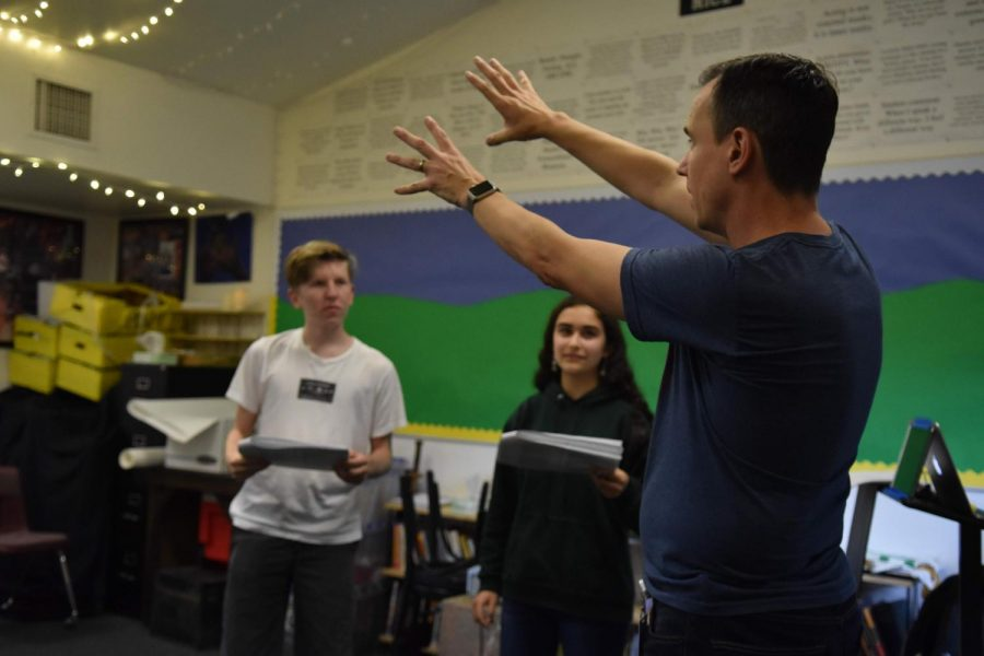 Director+Jeffrey+Draper+explains+the+layout+of+a+scene+to+the+cast+during+rehearsals.+The+play+is+five+acts+long+and+has+a+run+time+of+about+two+hours.