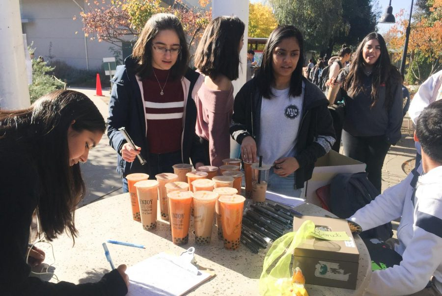 Red Cross Club officers Andrea Simonian (11) and Abha Patkar (12) sell boba from Teaspoon outside Manzanita. This week, Harker UNICEF also sold boba to raise money to support the Syrian refugee crisis.