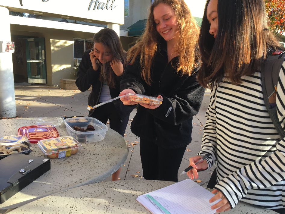 "Cassandra Ruedy (10), Charlotte Blanc (10) and Katelyn Chen (10) examine the treats Make a Birthday Wish Club is selling outside Manzanita. ""A birthday is a special thing that we all get to celebrate, and we want to make their birthdays as special as possible,"
